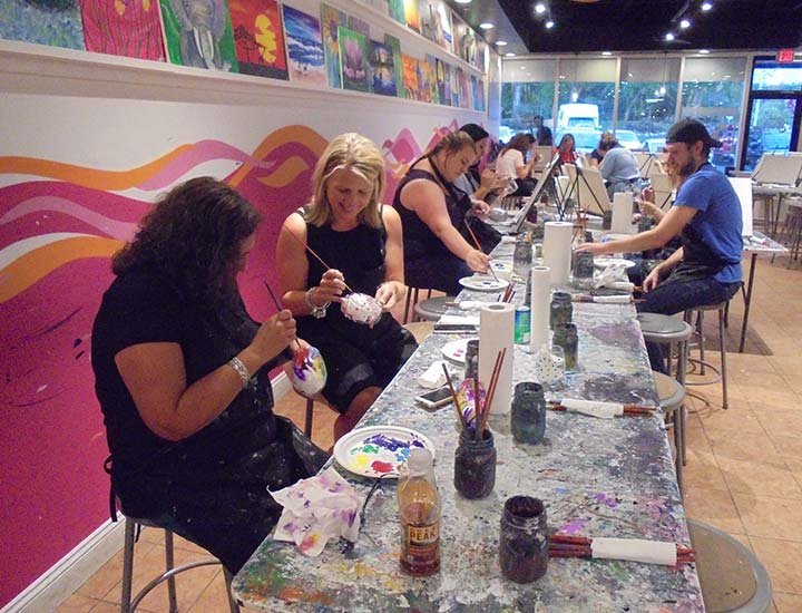 painters painting on pottery at a too cool for canvas paint & sip party