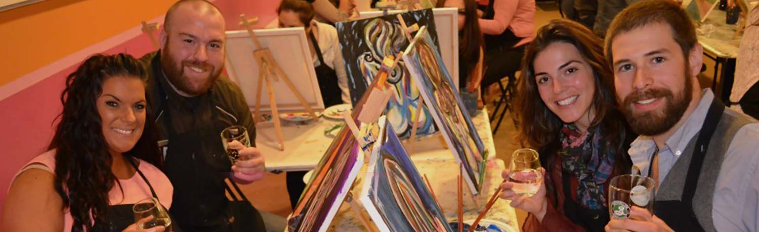 two couples drinking and painting at a paint & sip event