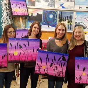four women holding up their completed paintings at a paint & sip adult party