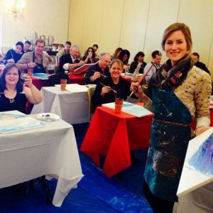 a paint & sip artist and customers at a paint & sip travel event