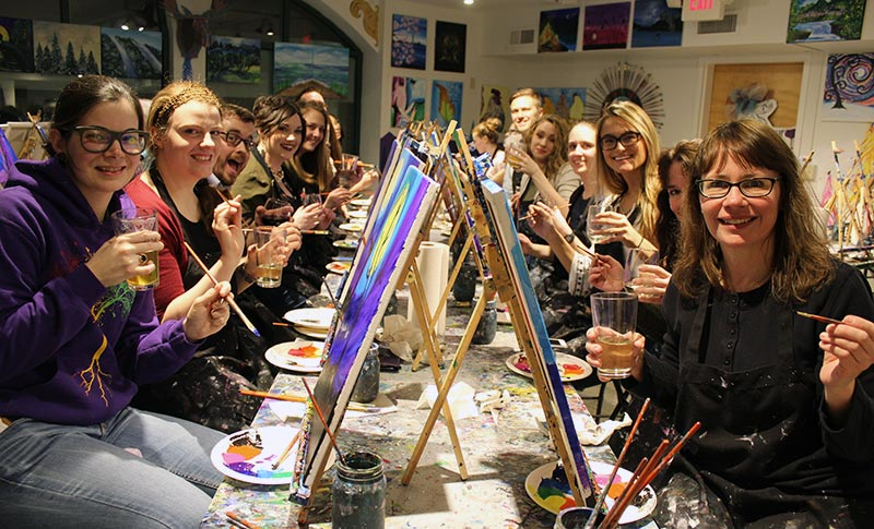 a group of men &women drinking beer and wine and painting at the Burlington Paint & Sip Studio